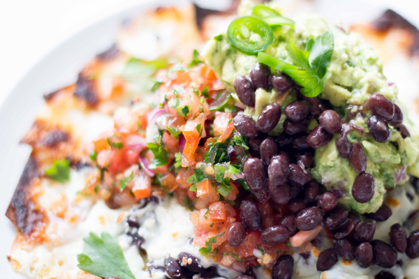 This vegetarian homemade nachos recipe is made with melted mozzarella cheese, black beans, pico de gallo, and homemade guacamole. It's definitely a meal your whole family will enjoy! | www.seriousspice.com
