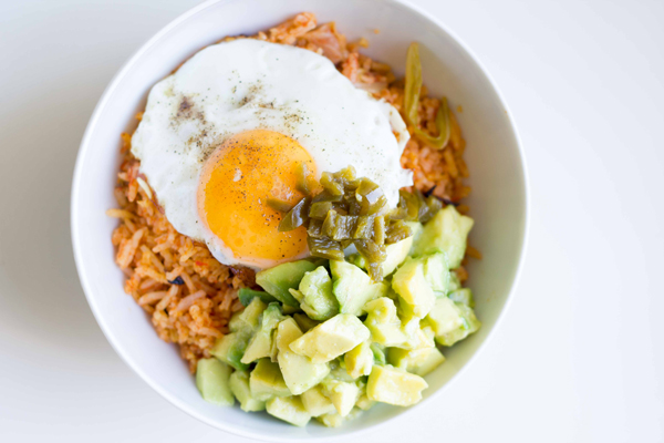 This yummy rice bowl recipe is made with spicy tomato cabbage rice topped with diced avocado, pickled jalapeños and a fried egg! | www.seriousspice.com